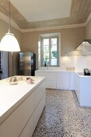 Pendant lamp above white kitchen counter and L-shaped counter in background in traditional interior