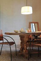 Pendant lamp above rustic wooden table with chunky turned legs