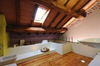 White installations, sloping ceiling with exposed wooden structure and skylight in modern bathroom with larch flooring