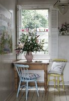 Kitchen chairs at rustic wooden table in corner below window with open white shutters