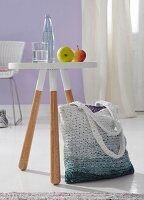 A striped crocheted shopping bag with a colour gradient next to a dip-dyed style stool