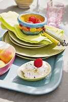 Cream cheese and fresh fruit in a bowl and on a plate on a tray