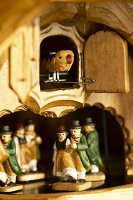 Detail of cuckoo clock with bird and dancing figurines in traditional costumes
