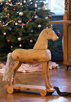 Old-fashioned Christmas toys: antique wooden pull-along horse in front of Christmas tree