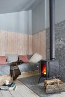 Fireplace in comfortable living area of old wooden house with high sloping ceiling