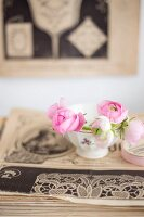 Pink ranunculus in bowl on stack of old yellowed magazines