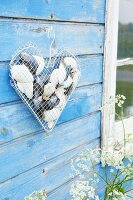 Love heart made from wire mesh and wire coathanger filled with shells and hung on board wall