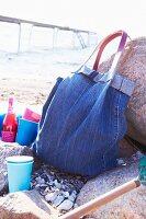 Denim bag and colourful beakers on beach