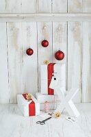 Gifts wrapped in red and white, red baubles and white X ornament in front of board wall