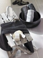 Shaving mirror on wooden bench and rolled towels in black bowl in bathrom