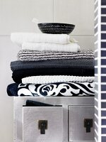 Stacked, monochrome towels on top of silver Oriental cabinet