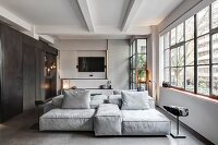 Sofa combination and factory windows in industrial loft apartment in shades of grey