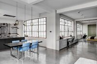 Concrete floor, factory windows, dining table and blue chairs in industrial loft apartment in shades of grey