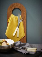 Yellow napkin and cutlery hanging from wooden board with hole