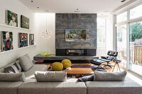 Fireplace in stone-clad chimney breast, corner sofa and glass wall in modern interior