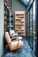 Two retro armchairs in front of wall-mounted shelved in glass house
