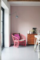 Pink rattan armchair and retro chest of drawers against pink wall