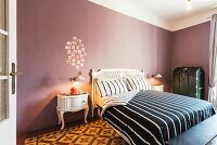 Antique bed, black and white striped bed linen and arrangement of photos on mauve wall in elegant bedroom