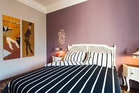 White double bed with black and white striped bed linen against mauve wall