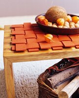 Autumnal arrangement on woven, orange felt mat on wooden table above basket of firewood