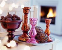 Colourful metallic candlesticks and artistically decorated baubles on tray next to bowl of fruit