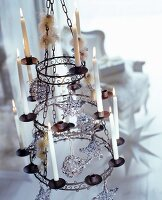 Vintage candle chandelier decorated with Christmas tree baubles and lit candles