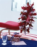 Poinsettia garland on cantilever chair and wrapped gifts