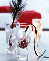 Branch and red bauble in decorated drinking glasses