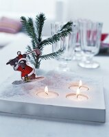 Festive cartoon figurine, artificial snow and sprig of fir on tealight holder with tealights in recesses