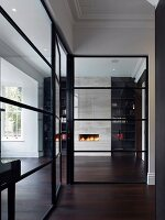 View of fire in fireplace seen through glass wall with black lattice structure