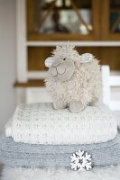 Plush sheep on stack of woollen blankets