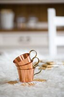 Stacked copper cups on painted seagrass coasters