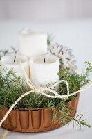 Pillar candles and evergreen twigs in copper cake tin