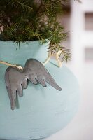 Metal angel's wings hung on turquoise plant pot