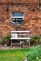 White bench in garden against brick façade