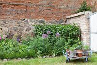 Plant pots in hand cart in front of stone and brick façade and flowerbed