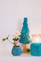 Christmas arrangement of turquoise needlework and small hellebore plant