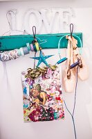 Colourful Christmas gift bag, ballet shoes and headphones hanging from vintage coat rack painted turquoise