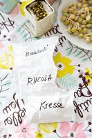 Labelled seed packets on floral paper surface and sprouting seeds in tin and on plate