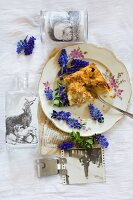 Crumb cake and grape hyacinths arranged on vintage plate