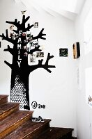 Rustic wooden staircase and black family tree painted on white wall and decorated with family photos