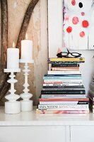 Lit candles in two white candlesticks and stacked books on sideboard