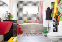 Red sink, black chest of drawers and fitted bathtub in bathroom with chequered wall tiles
