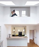 Counter in fitted kitchen below modern gallery with glass balustrade and skylights