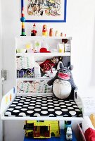 Baby-changing cabinet with black and white polka-dot mat next to shelves of toiletries and toys