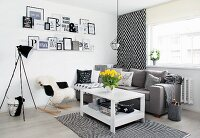 Wooden table, grey couch and framed messages in corner of black and white living room