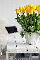 Bouquet of yellow tulips on white wooden coffee table