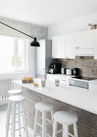 Kitchen counter with white worksurface and white bar stools against rustic wooden cladding