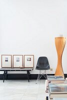 Black classic chair next to console table and framed pictures in minimalist, retro interior