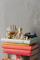 Retro toys and miniature figurines on stacked books against grey wall